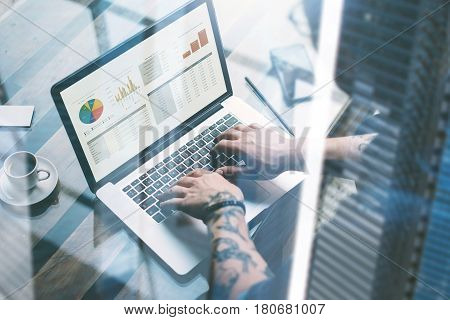 Tattooed coworker in eyeglasses working at sunny office on laptop while sitting at wooden table.Businessman analyze graphs and diagramm on notebook screen.Blurred background.Double exposure concept