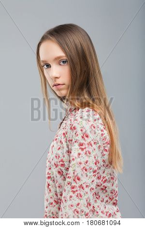 Young beautiful blond model girl in blouse with a pattern of flowers. Long straight hair and deep blue yeys. Emotionless