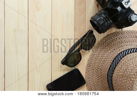 Summer travel equipmentmen's hatsCamera and Sunglasses on wooden floor and have copy space.