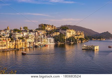 The Famous City Palace On Lake Pichola Reflecting Sunset Light. Udaipur, Travel Destination And Tour