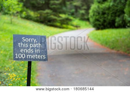 Sign in garden stating path ends in 100 meters