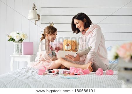 Mother is watching her daughter reaction on reading a book. She is holding a white and probably reading something to her daughter who is laughing at that moment
