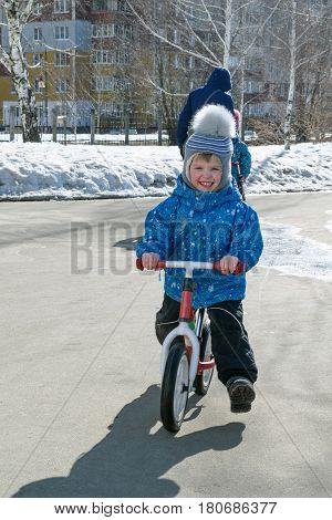 The little boy in jacket pants and hat with bubo rides balance bike on the asphalt. The boy is happy. He learned to ride balance bike. He rides in a spring Sunny day.