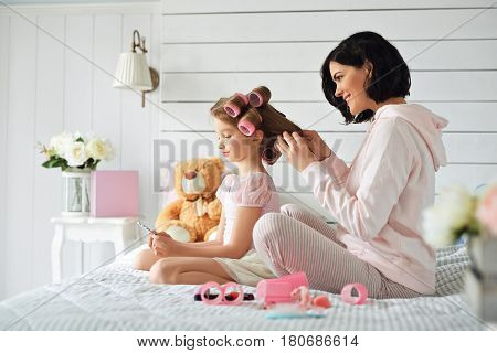 Pretty mother is curling her daughter's hair while she is staring herself in the pocket mirror. Woman and girl are are sitting on a bed