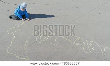 The little boy in jacket hat trousers sits on the pavement and draw a long winding line of yellow chalk. From the boy on the pavement falls the shadow.