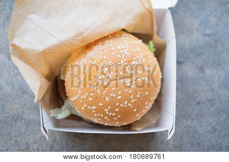 Hamburger is a fast food make from bun meat cheese and vegetable in white paper box