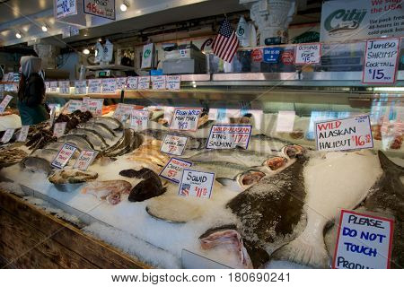 SEATTLE, WASHINGTON, USA - JAN 24th, 2017: Customers at Pike Place Fish Company wait to order fish at the famous seafood market. This market, opened in 1930, is known for their open air fish market style