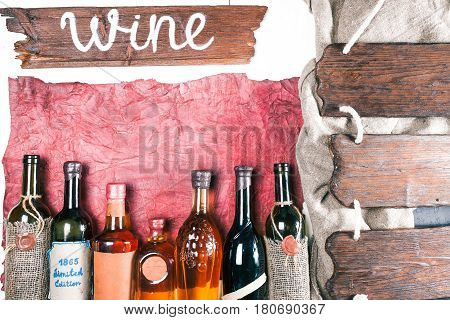 Row of various vintage wine and brandy bottles on old textured paper. Triple signboard on ropes on the side. Rustic signboard with text 'Wine' as title. Retro style. Top view
