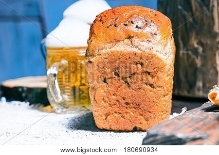Mugs of beer and bread loaf on raw wood pub counter with natural stumps and burlap