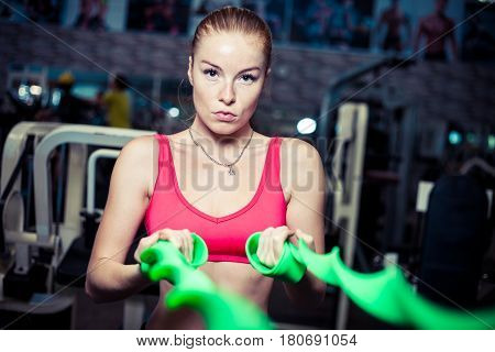 Serious young woman workout with rubber bands at fitness gym.Pretty athletic girl uses green stretch band while exercising in a fitness center.
