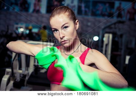 Charming young woman workout with rubber bands at fitness gym.Pretty athletic girl uses green stretch band while exercising in a fitness center.