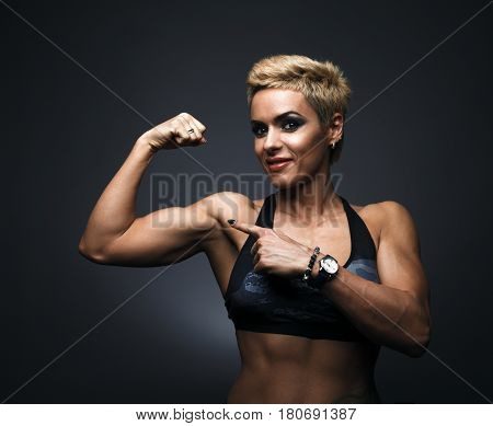 Cheerfully smiling sporty woman demonstrating biceps, on dark background