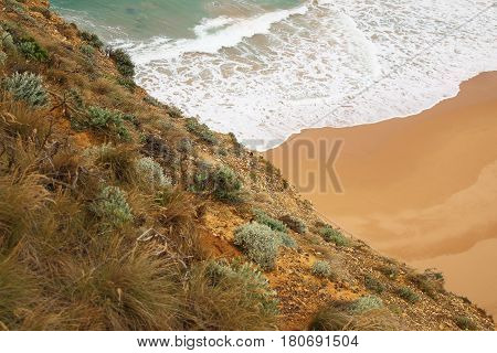 At the edge of the cliff where the ocean meets the beach