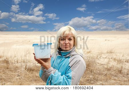 A woman and a geocaching container at the beach