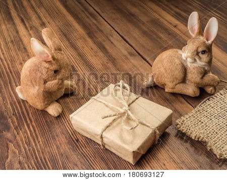 Easter bunnies on the background of wooden table from the old boards with burlap, gift box tied with string and brown chicken eggs. Background in rustic style for advertising or Easter greetings