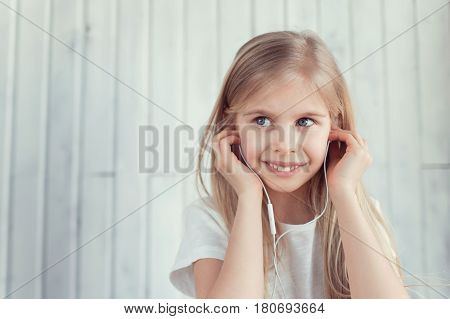 Smiling girl is listening to the music and due to her eyes it seems like she is thinking about something. She is in her earphones and her look has side direction
