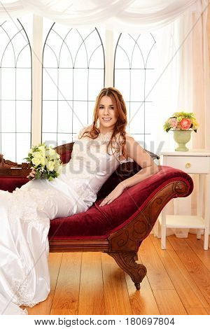 portrait of bride sitting on fainting couch by window