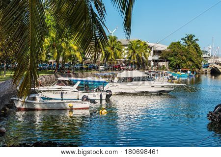 Victoria Mahe Seychelles - December 16 2015: Boats resting at the colourful palm-lined Victoria Harbour in Mahe Island Seychelles Indian Ocean Africa.