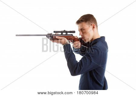 A young adult aimng down the sight of a rifle