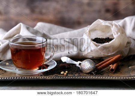 Cup of tea with spices and strainer on tray