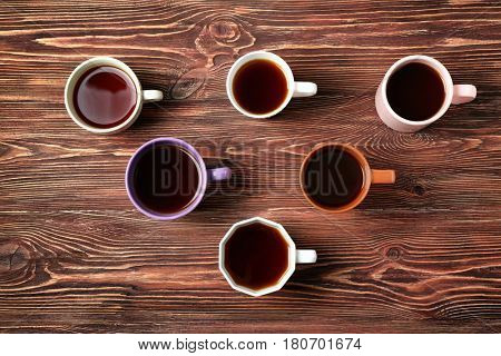 Delicious tea in cups forming triangle on wooden background