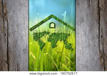 Earth Day. Ecology concept. Nature concept. Green map of the world under the roof is protected from contamination and industrial waste on background fresh green spring grass with dew drops through the old wooden fence.