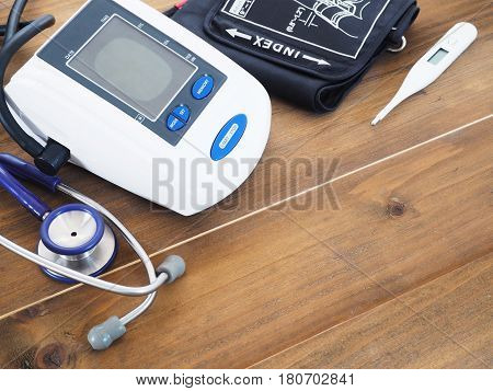 Digital Blood Pressure Monitor stethoscope and thermometer on wood background primary healthy check