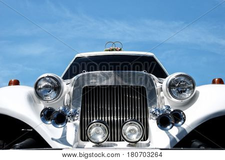 Odessa, Ukraine, 26 july 2009 - retro limousine decorated with flowers waiting wedding ceremony, closeup front view,  clear sky as background