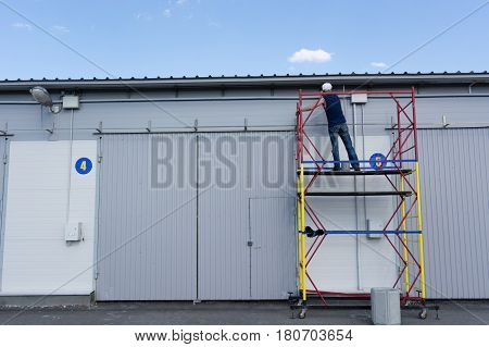 the man paints a metalframework from the construction woods. the builder works at height. construction works