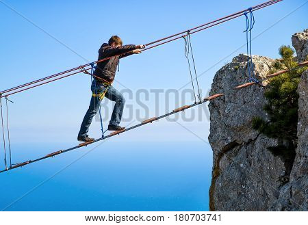 CRIMEA, RUSSIA - MAY 19, 2016: Tourist walking on rope bridge on the Mount Ai-Petri over the sea. Ai-Petri is one of the highest mountains in the Crimea and tourist attraction.
