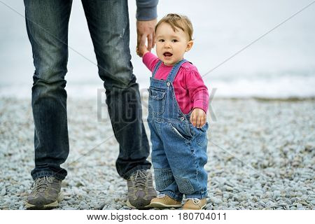 Baby girl and her father on the sea beach. Father holds daughter's hand.