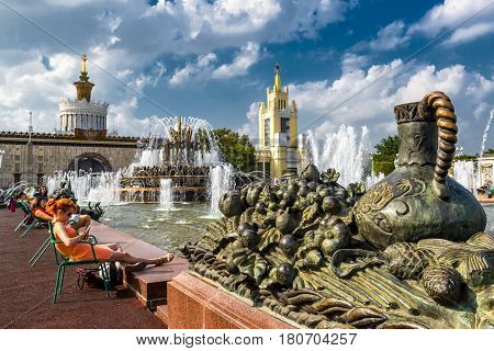 MOSCOW - JULY 29, 2016: Tourists are resting near the Stone Flower Fountain in All-Russia Exhibition Center (VDNKh). This fountain was built in 1954.
