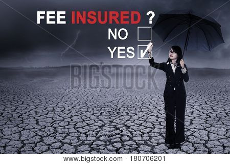 Picture of a beautiful businesswoman using an umbrella while answering yes to a question of fee insured