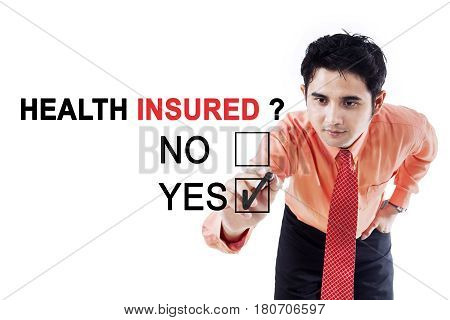 Picture of young businessman using a pen while selecting a yes option to a question of health insured on the whiteboard