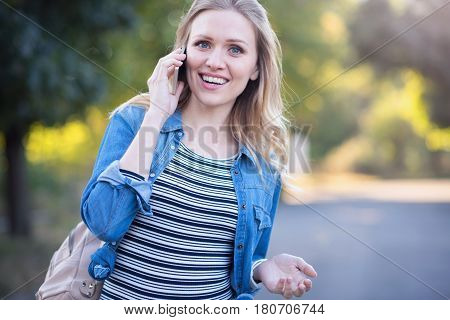 Full of joyfulness . Positive optimistic pregnant woman walking in the park while expressing happiness and enjoying conversation on the phone