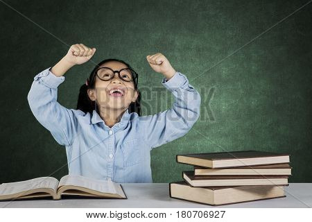 Portrait of cheerful schoolgirl sitting with book on desk while celebrating her success