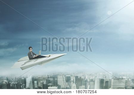 Picture of a male college student sitting on a paper plane while using a laptop computer and flying above a city