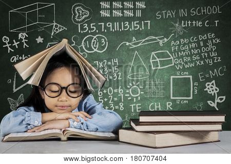 Portrait of cute schoolgirl reading a textbook with doodle and scribble on the chalkboard