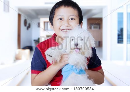 Portrait of little boy hugging Maltese dog while smiling at the camera and standing in the living room