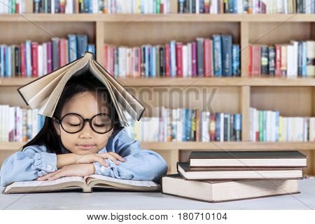 Portrait of little girl sitting in the library while reading a book with a textbook over her head