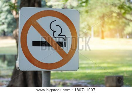 no smoking metal sign in the park. bicycle, sign