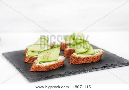 Snacks with cheese feta and cucumber on shale board. The concept of food and vegetarianism.