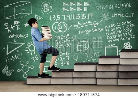 Image of primary student carrying pile of book while walking on book stair with doodle and scribble on chalkboard