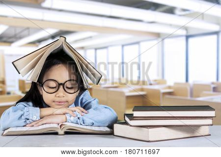 Portrait of primary student reading a textbook while sitting with a book over her head in classroom