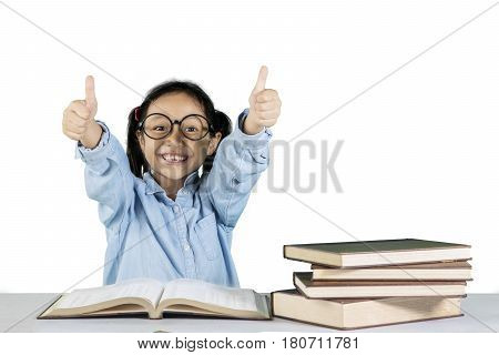 Portrait of primary student showing ok gesture with book on the desk isolated on white background