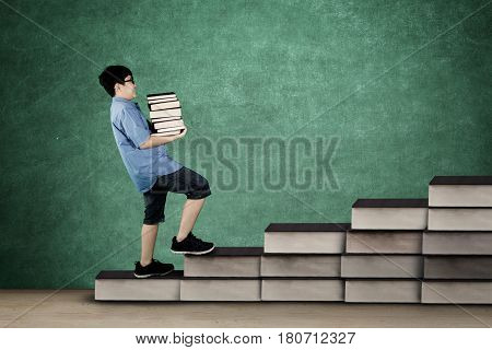Image of schoolboy walking on staircase while holding pile of book with chalkboard