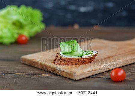 Sandwich with cucumber and feta cheese in wooden board. The concept of food and vegetarianism.