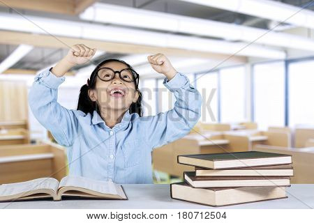 Portrait of schoolgirl sitting with book on desk while lifting hands as her success expression in classroom