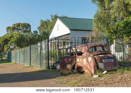 NIEU BETHESDA SOUTH AFRICA - MARCH 22 2017: An historic old house and car wreck with numberplate Roesemaat (rust friend) in Nieu-Bethesda an historic village in the Eastern Cape Province