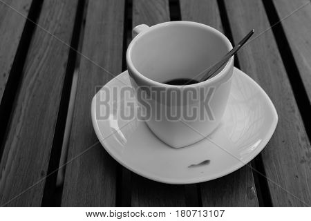 Dirty coffee cup after drinking in the morning with wooden table background. (Black and White effect)
